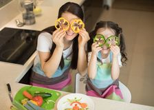 Mother and kid daughter having fun in the kitchen. Mother and daughter having fun in the kitchen Royalty Free Stock Photos