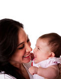 Mother and Daughter having fun laughing. Faces of beautiful family couple of mother and daughter baby girl looking at eachother having fun and laughing, isolated stock photography