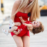 Mother and daughter having fun outside on the dock Stock Photos