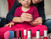 Mother and daughter having fun painting fingernails Royalty Free Stock Image