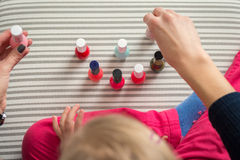 Mother and daughter having fun painting fingernails, view from above Royalty Free Stock Images