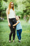 Mother and daughter having fun in the park. Daughter hug mother leg aginst summer background Royalty Free Stock Image