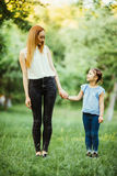Mother and daughter having fun in the park. Happy family concept. Beauty nature scene with family outdoor lifestyle. Happy family Stock Photo