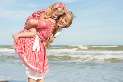 Mother and daughter having fun playing on the beach Royalty Free Stock Photo