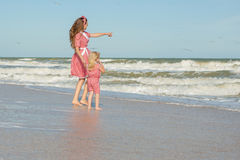 Mother and daughter having fun playing on the beach Stock Photography