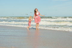 Mother and daughter having fun playing on the beach Royalty Free Stock Image