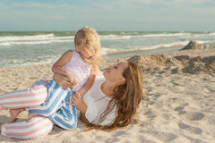 Mother and daughter having fun playing on the beach Stock Images