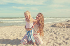 Mother and daughter having fun playing on the beach Royalty Free Stock Photos
