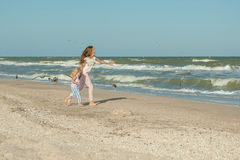 Mother and daughter having fun playing on the beach Stock Image