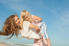 Mother and daughter having fun playing on the beach Royalty Free Stock Images