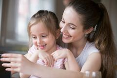 Mother and daughter having fun playing smartphone together stock photos