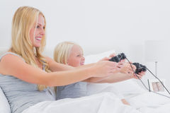 Mother and daughter having fun playing video games. In bed Royalty Free Stock Images