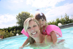 Mother and daughter having fun in pool. Mother and daughter playing in swimming-pool Royalty Free Stock Photo