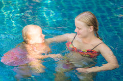 Mother and daughter having fun in pool at tropical beach resort Stock Photos