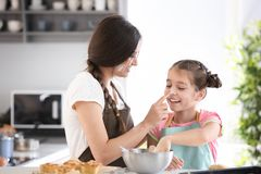 Mother and daughter having fun while preparing dough Stock Image