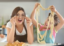 Mother and daughter having fun while preparing dough Stock Images