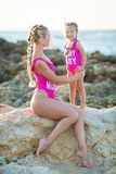 Mother daughter having fun resting on the rocky beach wearing pink swimming suits. Blond lady with girl enjoy summer time together stock photography