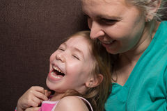 Mother And Daughter Having Fun On Sofa Stock Photo