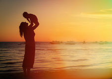Mother and daughter having fun at sunset beach Royalty Free Stock Photo