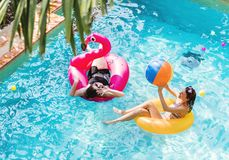Mother and daughter having fun in the swimming pool stock photos