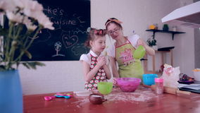 Mother and daughter having fun together making cookies in the kitchen.