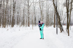Mother and daughter having fun in the winter park Stock Photo