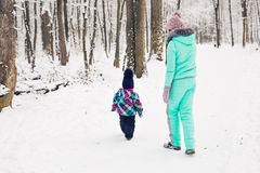 Mother and daughter having fun in the winter park Royalty Free Stock Photo