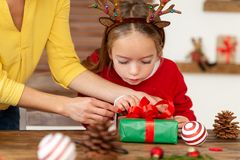 Mother and daughter having fun wrapping christmas gifts together in living room. Candid family christmas time background royalty free stock photography