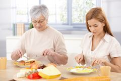 Mother and daughter having lunch at home. Senior mother and adult daughter having lunch together at home stock images