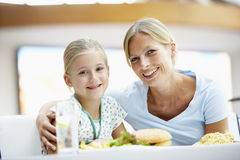 Mother And Daughter Having Lunch Together At Cafe. Mother And Young Daughter Having Lunch Together At Cafe Stock Photo