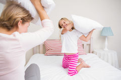 Mother and daughter having pillow fight Stock Images