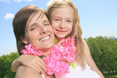 Mother with is daughter having a pink necklace Stock Photos