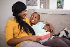 Mother and daughter having popcorn while resting on sofa at home Royalty Free Stock Photography