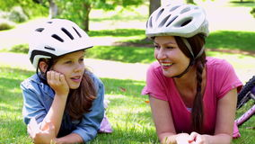Mother and daughter having a rest on their bike ride in the park. On a sunny day stock footage