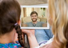 Mother and daughter having a video call with father in digital tablet Stock Photo