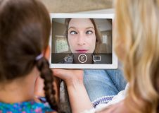 Mother and daughter having video calling in lving room Stock Image