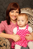Mother and daughter on her lap sitting in armchair. Interior in retro style Stock Image