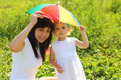 Mother and daughter hide under an umbrella Stock Images