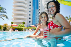 Mother and daughter hide under umbrella in pool Royalty Free Stock Images