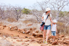 Mother and daughter hiking at scenic terrain Stock Photo