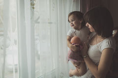 Mother and daughter in his arms waiting for dad looking out the Royalty Free Stock Image