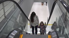 Mom and daughter are holding hands while standing on the escalator climbing up. Mother and daughter hold hands while standing on the escalator climb up. The stock video footage