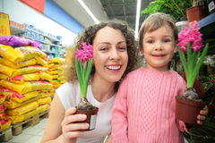 Mother and daughter hold pots with flowers in shop Royalty Free Stock Images