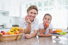 Mother and daughter holding apples Stock Images