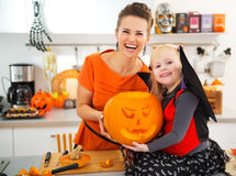 Mother with daughter holding big orange pumpkin Jack-O-Lantern Royalty Free Stock Photo