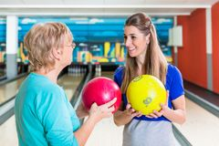 Mother and daughter holding bowling ball. Smiling mother and daughter holding bowling ball enjoying indoor game royalty free stock photography