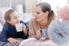 Mother and daughter holding cups Stock Photo