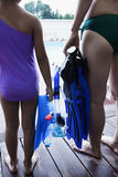 Mother and daughter holding flippers and snorkeling mask by the pool, low section Royalty Free Stock Photo