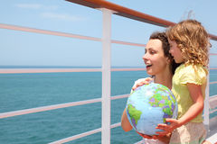 Mother and daughter holding globe on cruise liner Stock Photography