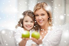 Mother and daughter holding green apples Stock Images